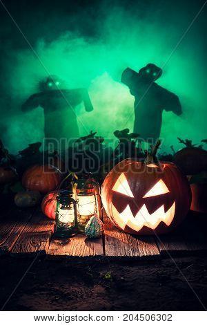 Orange Halloween Pumpkin On Dark Field With Scarecrows