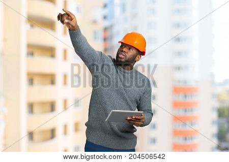 Construction supervisor on building background. Worker with orange helmet and grey sweater pointing on top, working on a project. Young engineer checking the interior with computer tablet.