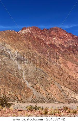 Pequeno povoado aos pés da montanha, com céu azul