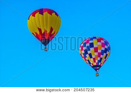 Two Hot Air Balloons Against Blue Background