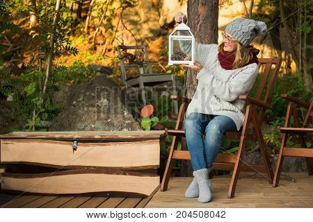 Woman in a wool sweater and a wool hat decorates the backyard and holds a decorative lantern in her hands. A girl is resting in the garden near the house.