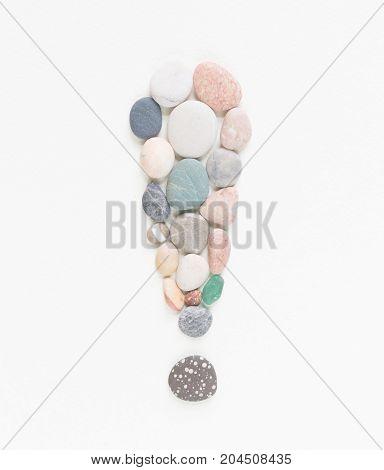 Sea pebbles, sea stones exclamation point. Sea pebbles background.