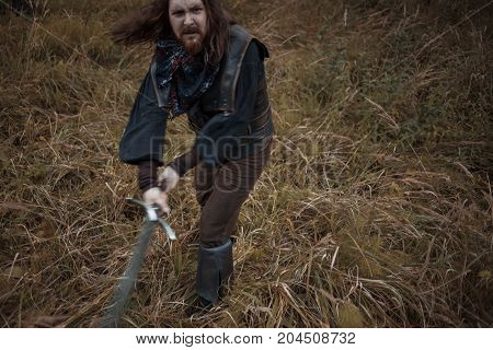 The bearded man knight. A guy in a medieval costume with a sword