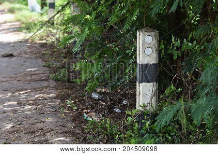 old traffic barrier pillar beside dirty asphalt road in countryside in thailand