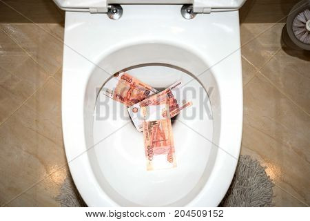 flush money in the white toilet by water