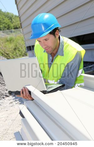 Engineer with laptop computer on building site