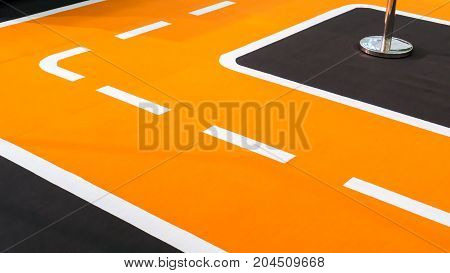 Curve of orange running track and lanes. Temporary setup detail on carpet floor.
