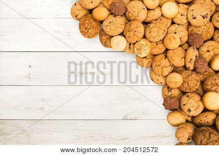 Cookies and biscuits sweets on white wood, background with copy space. Oatmeal and chocolate drops pastry border, dessert for tea.