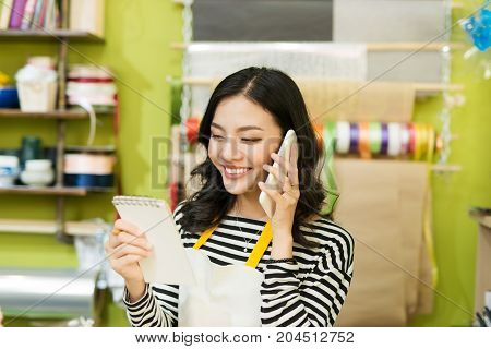 Smiling Asian Male Florist Calling On Smartphone And Making Notes At Flower Shop Counter