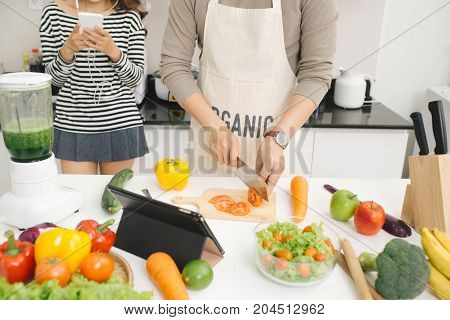Handsome Asian Man Chopping Vegetables In The Kitchen