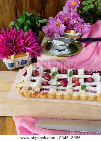 Strawberry pie with dough lattice covered with sugar powder surrounded by flowers