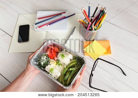 Healthy business lunch in the office, hands of eating person. Salad plate with vegetables on white wooden desk near mobile phone and open organizer. Snack at break time