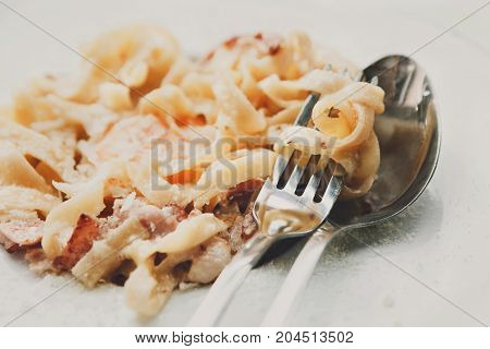 Traditional italian carbonara pasta with bacon, egg yolk and parmesan decorated with basil on white round plate. Restaurant food closeup with fork and knife. Filtered image