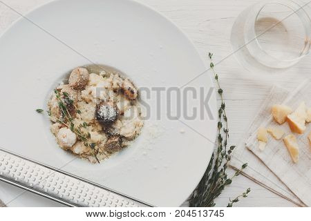Wild mushrooms porcini risotto with rosemary and grated parmesan cheese. Traditional italian cuisine dish. Restaurant food closeup. Forest fungus with rice. Top view, vertical composition