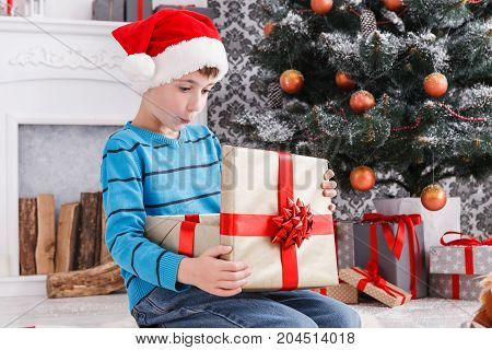 Cute surprised boy in santa hat unwrap christmas present on holiday morning in beautiful room interior. Male child open Xmas gifts near big decorated fir tree and fireplace. Winter holidays concept