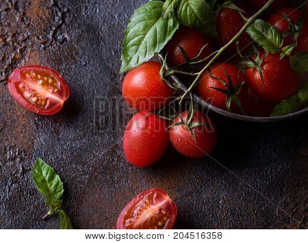 Fresh grape tomatoes with basil for use as cooking ingredients with a halved tomato in the foreground. Dark rusty metal backround. Copyspace