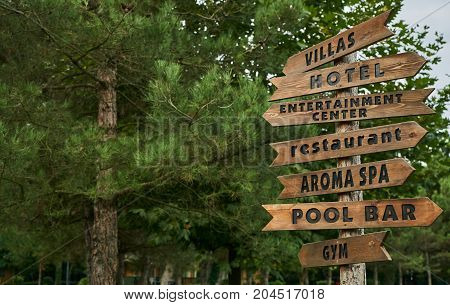 Wooden street signs in the recreation center. Blank street sign post. Crossroad signpost with directions to villas hotel entertainment center restaurant aroma spa pool bar and gym