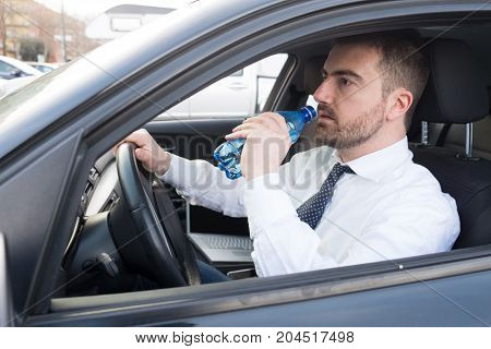 Man Drinking Water Seated In Car
