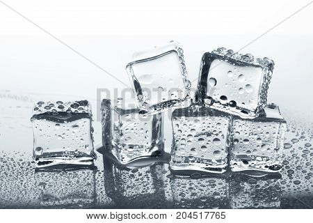 Transparent ice cube with reflection and water drops on glass background. Closeup of cold crystal blocks group cutout