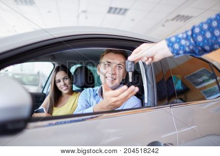 Young family comes into Car dealership to choose the car to buy it.