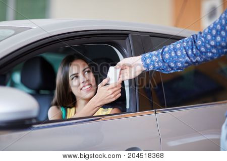 Beautiful young woman is talking to handsome car dealership worker while choosing a car in dealership.