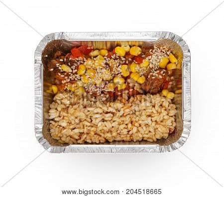 Healthy lunch in foil container. Healthy food take away and delivery. Meat, corn, rice and sesame in box on white background, closeup, isolated