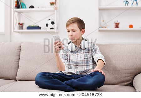 Teenager messaging to friends chat on mobile sitting on couch in living room at home. Stylish kid in checkered shirt and jeans with headphones on the neck