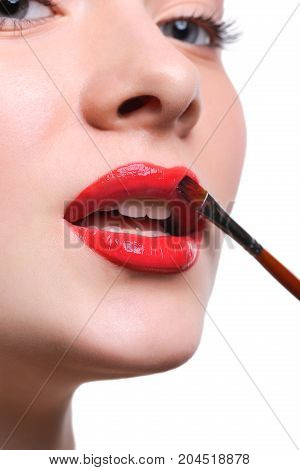 Lips makeup closeup. Apply lipstick with brush. Close-up of female model face with fashion glossy red make-up, beauty concept isolated