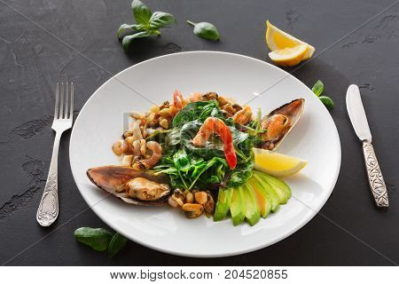 Warm salad with grilled seafood and cutlery. Plate with mix of roasted shrimps, mussels and squid, restaurant serving