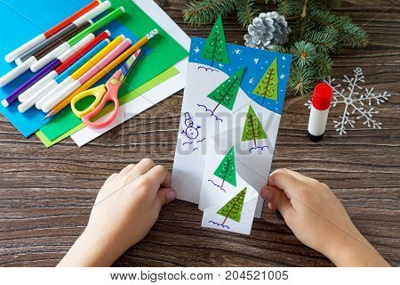 The Child Makes A Greeting Card Christmas. Made With His Own Hands. Children's Art Project Craft For