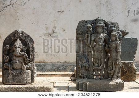 Mysore India - October 27 2013: Unearthed gray stone statues on display on the grounds of the Chennakesava Temple in Somanathpur. Set against filthy white wall showing Nandi and Vishnu with consort