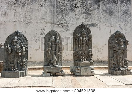 Mysore India - October 27 2013: Four gray stone statues on display on the grounds of the Chennakesava Temple in Somanathpur. Set against filthy white wall showing Vishnu and other deities.