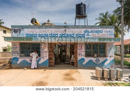 Mysore India - October 27 2013: Simple fresh milk collection building of government company in hamlet of Kethupura. Messages on wall. People black water tank and empty milk canisters. Under blue sky.