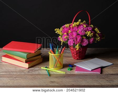 Concept of Teacher's Day. Happy Teacher's Day, pencils and pens in a glass, sprig with autumn flowers.