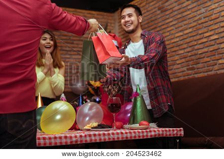 Hand boss office holding surprise with paper bag special gift for businessman in x'mas party new year celebrate