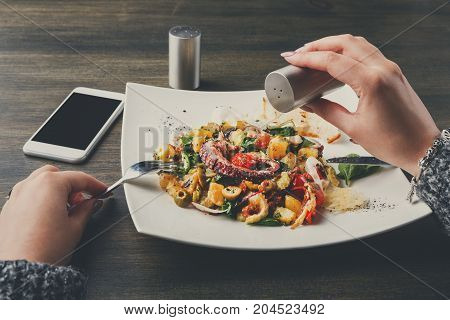 Salting salad with octopus and vegetables pov. Unrecognizable person seasoning appetizing fresh mediterranean seafood meal with toasts in restaurant