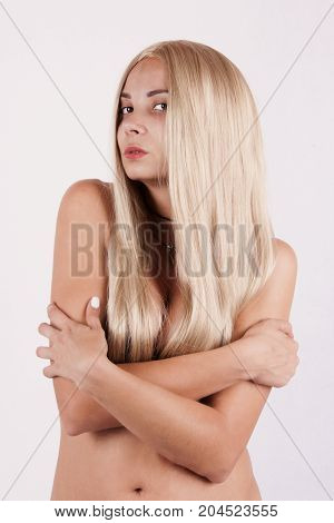 naked girl in a black livery with long blond hair crossed her arms over her chest against a white background