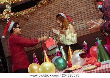 Hand boss office holding surprise with paper bag special gift for businesswoman in x'mas party new year celebrate