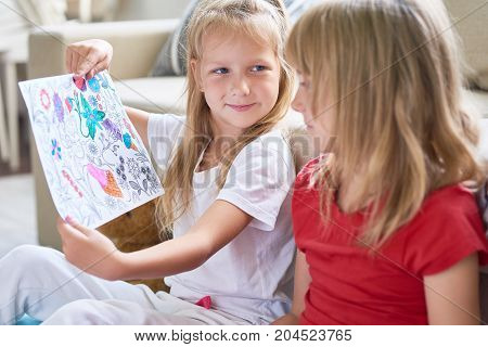 Satisfied little girl showing half-painted page from coloring book to her elder sister and waiting for her reaction, interior of cozy living room on background