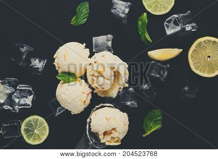 Ice cream scoops with ice cubes and lemon slices and scoop on black background. Delicious cold sweet dessert, close up