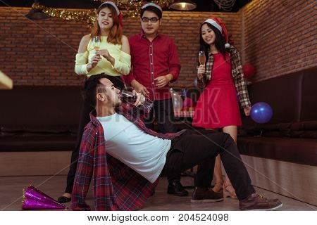 Young men and women group x'mas party together with drinking wine and soft drink dancing step show happy and fun in new year