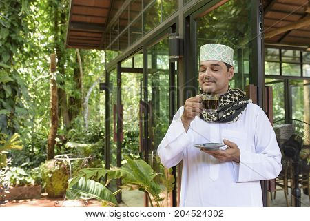Portrait of Arab muslim handsome man in white thobe with prayer cap and yashmagh on neck standing next to doorhand hold glass of black coffee and smell coffee.