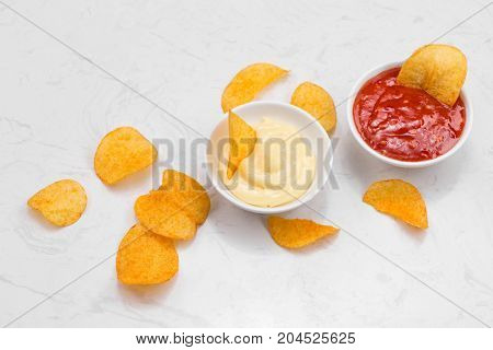 Concept of unhealthy food. Cheese and onion potato chips with hot chilli sauce on pink background.