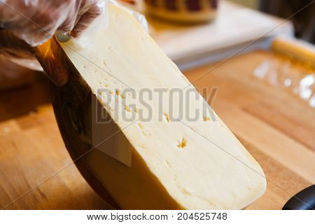 Gouda cheese closeup. Half wheel of cheese on wooden table. Shop assistant slicing cheese, background, copy space
