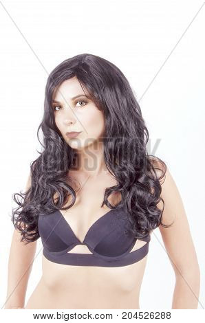 naked girl with long black hair in a black bra on a white background