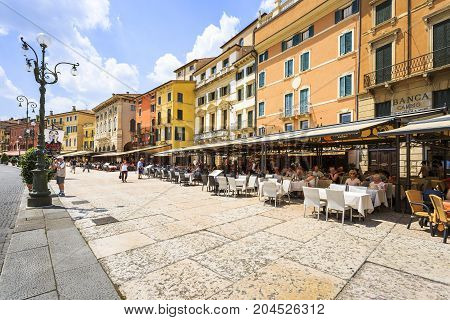 VERONA ITALY - JUNE 25 2016: Picture of the many colorful restaurants around the Piazza Bra with many tourists in a sunny day with clouds. Verona Italy.