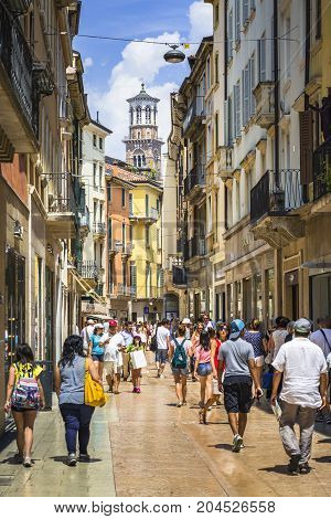 VERONA ITALY - JUNE 25 2016: Picture from Via Giuseppe Mazzini with many stores and tourists with Torre dei Lamberti in the background in a sunny day with clouds. Verona Italy.
