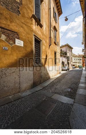 VERONA ITALY - JUNE 25 2016: Wide vertical picture of Via Sole a narrow street with colorful houses cars parked and no people in a sunny day with clouds. Verona Italy.