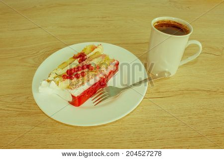 A cup of coffee and cake on wooden background. piece cake on white plate with fork - Retro color