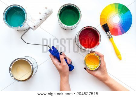Choosing color for painting. Hands hold brush and paint roller on white background top view.